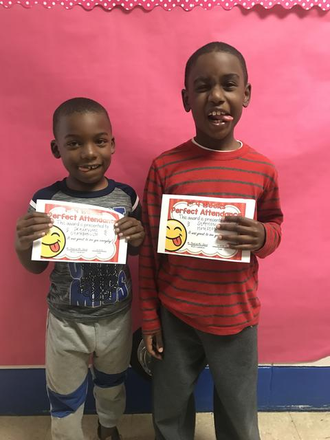Two males pose with certificates, being goofy and sticking out tongues