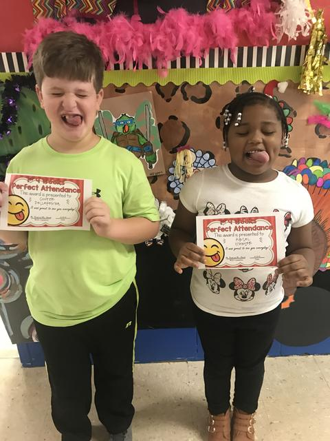 Male and female with certificates strike goofy pose with tongues out