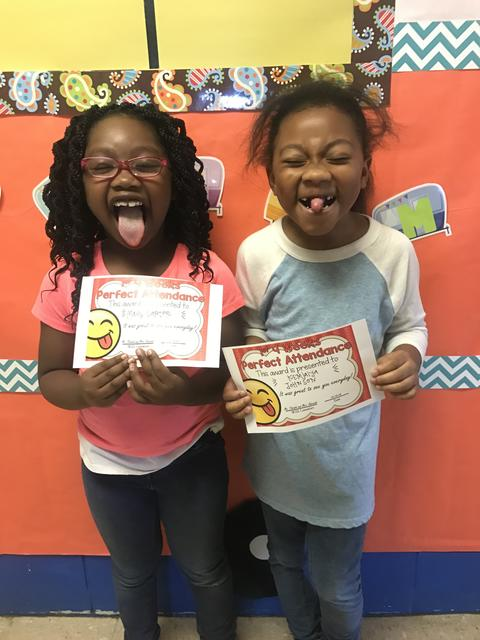 Two female students in goofy pose with tongues sticking out