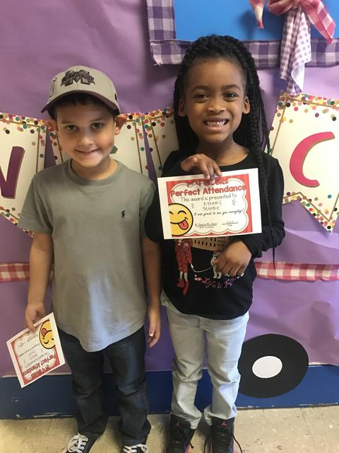 Students hold certificates and stand by purple bulletin board