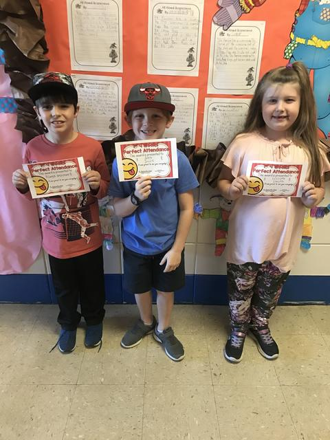 Three students smiling with certificates