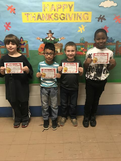 Four students holding certificates while standing by Thanksgiving bulletin board