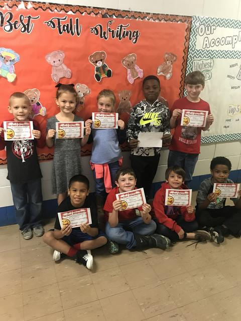 Large group with certificates by orange bulletin board