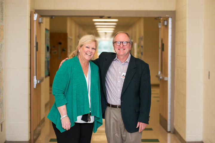 Members of faculty standing together in a hallway.