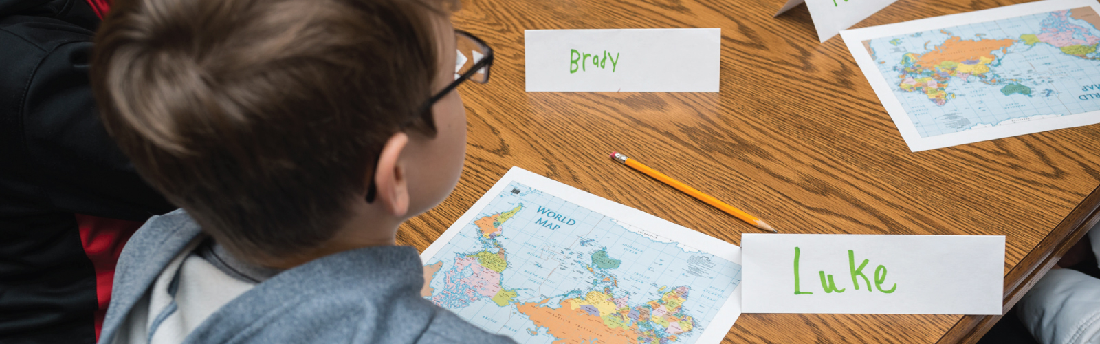 Student at a wood table with a world map in front of him
