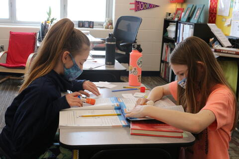 Students pasting number stories into math book