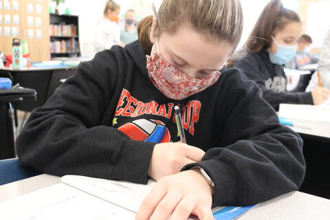 Student pasting number stories into math book