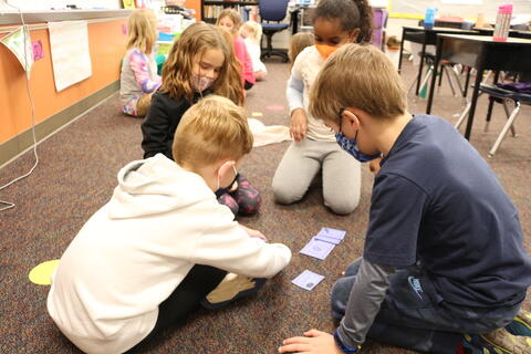 Students practice reading with flash cards