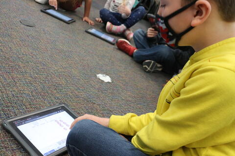 Students count coins using ipads