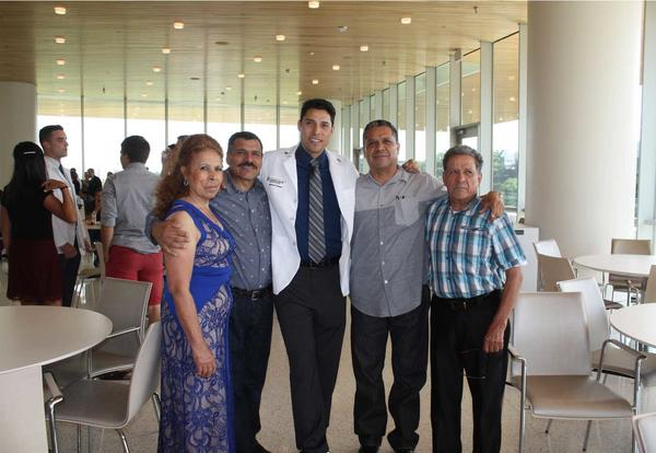 Armando poses with his family at his White Coat Ceremony at University