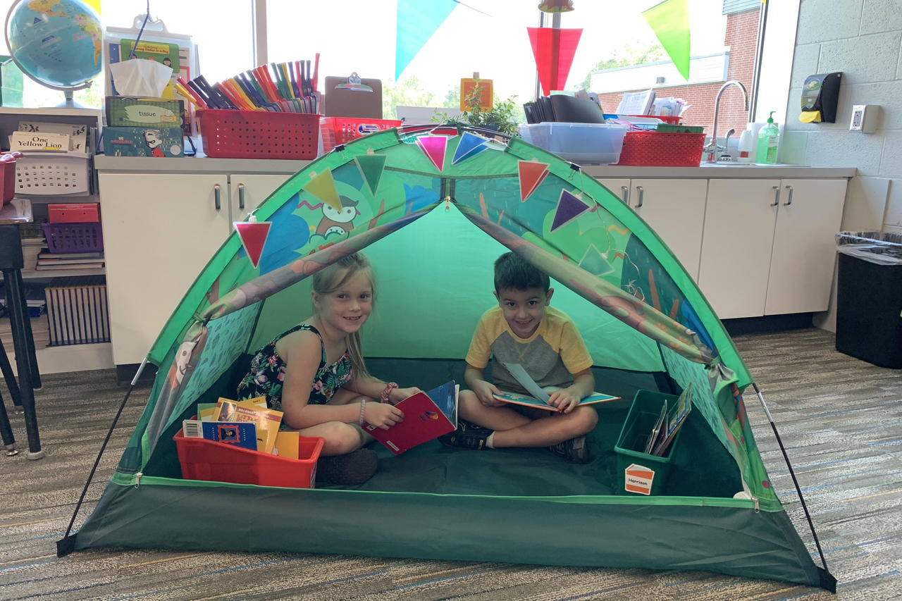 Kids reading in a tent