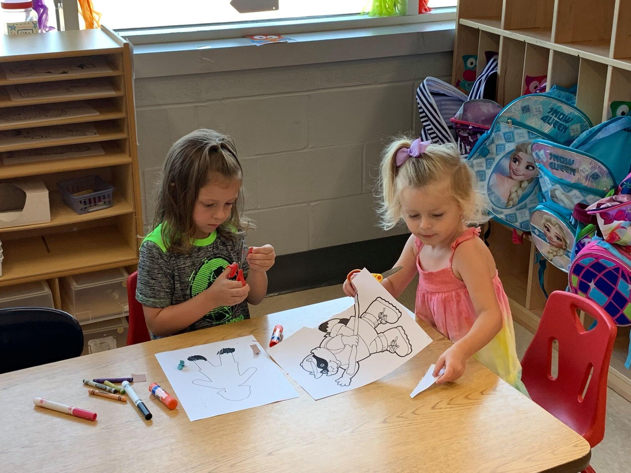 Two preschool aged girls sit together at table sharing markers and working on pictures.