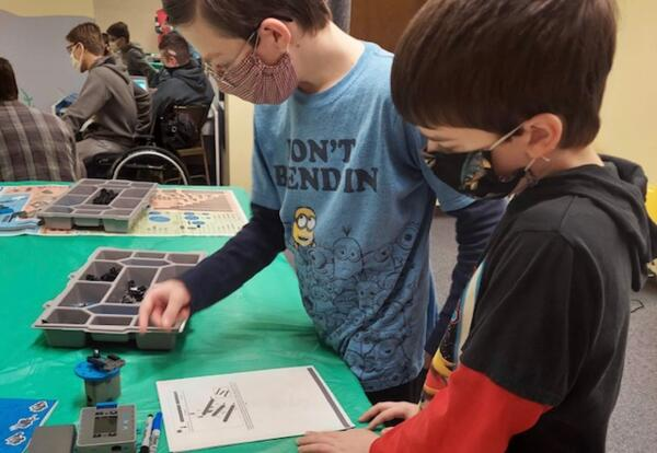 Two elementary aged boys work together to build a robot.