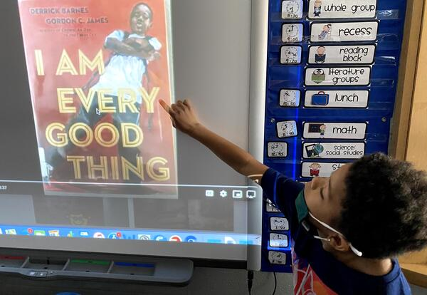 """A kindergarten boy points to a screen that shows a book cover with the title, """"I Am Every Good Thing."""""""