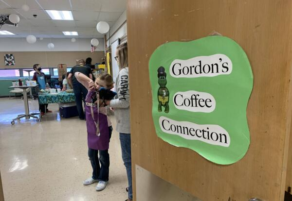 """A sign reading """"Gordon's Coffee Connection"""" is on an open door with eager students waiting inside."""