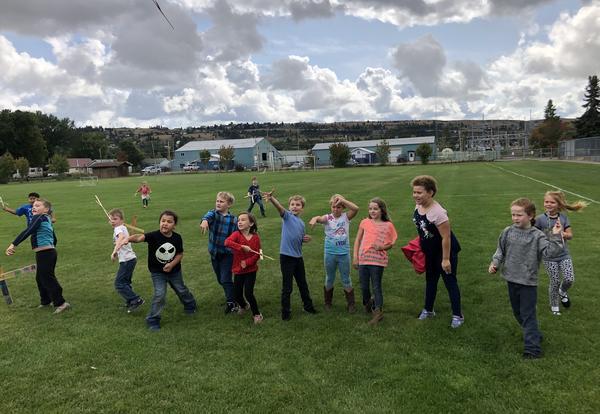 Second graders on a field throwing handmade boomerangs