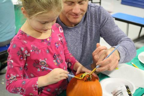 Picture of a family painting pumpkins