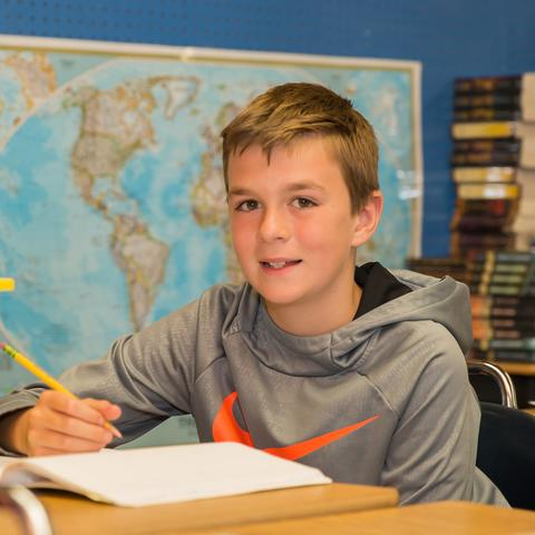 Elementary student sitting at deck with world map in background