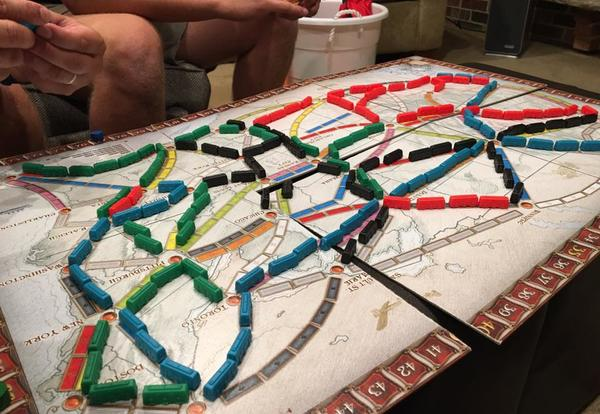 family playing ticket to ride board game