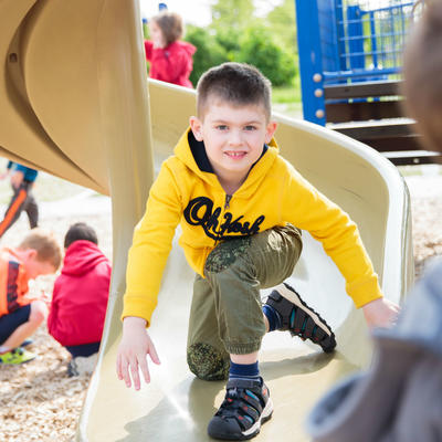 student on slide on playground