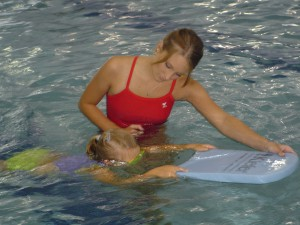Swimming instructor teaching a young student