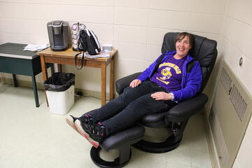 High School instructional aide Sheera Seegert takes a break in the massaging chair