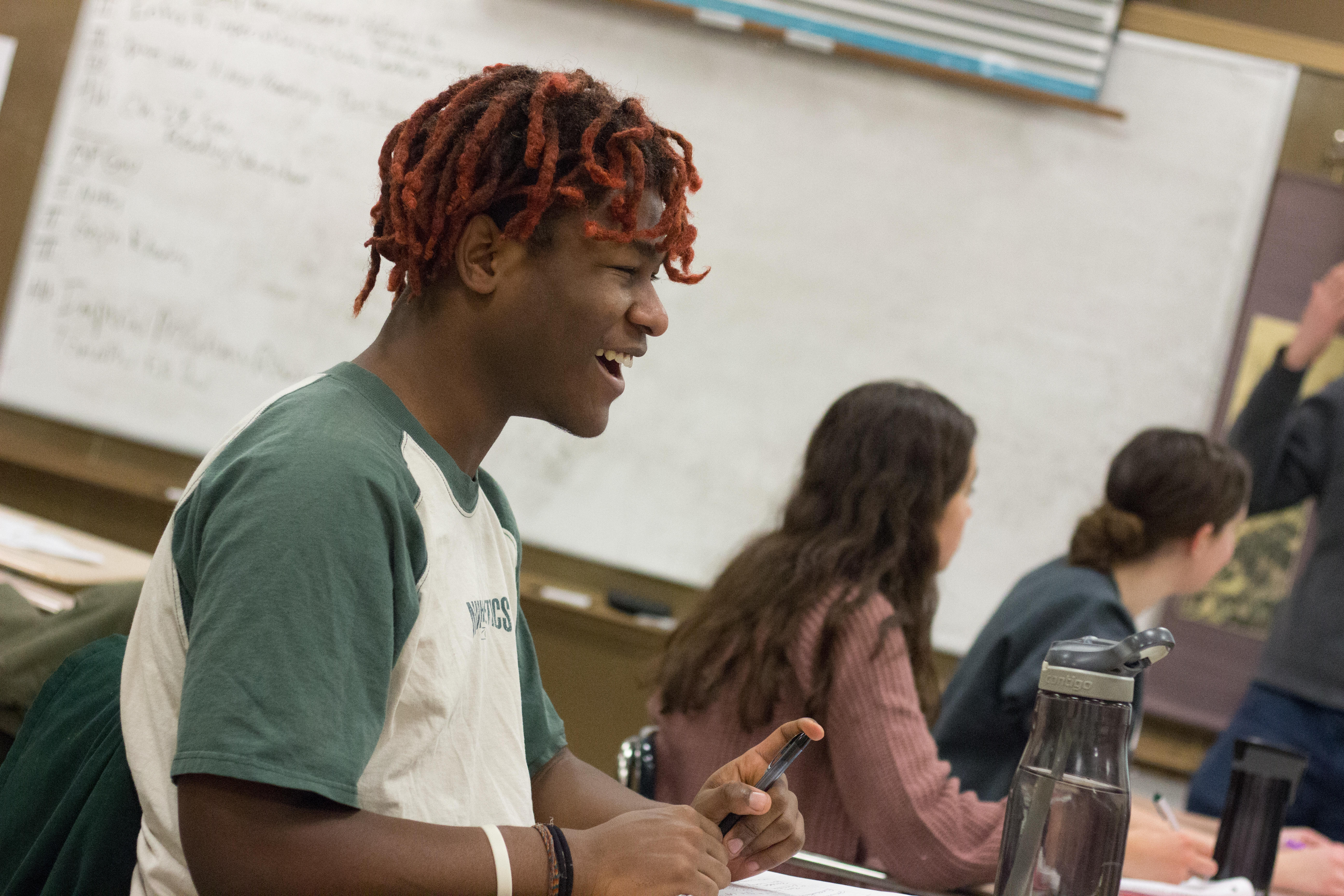 Student smiling while working in an Advanced Placement class.