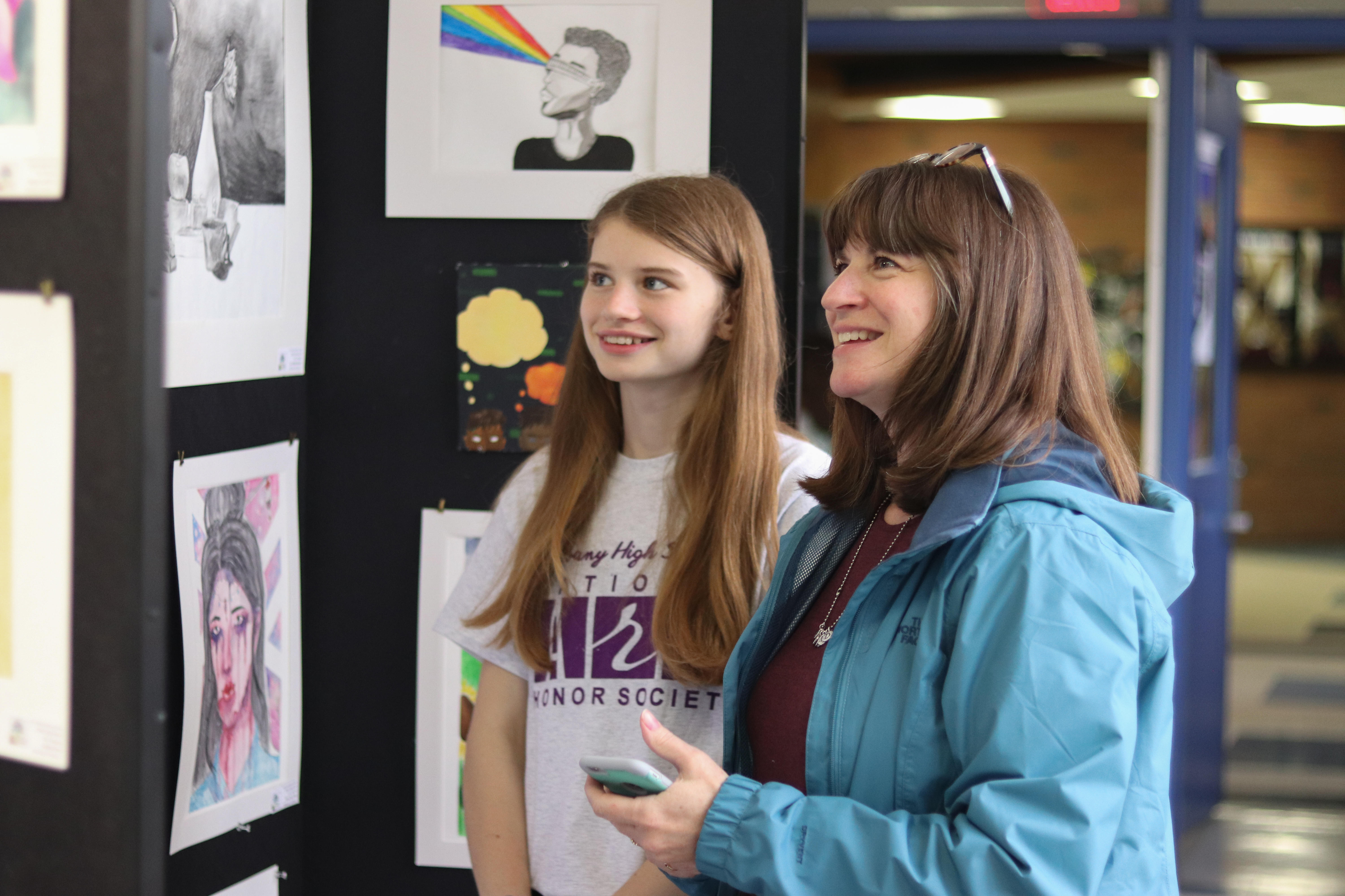 Female student and her mother admiring her artwork on display.