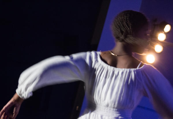 Picture of an ASH student dancing on stage in atmospheric lighting.