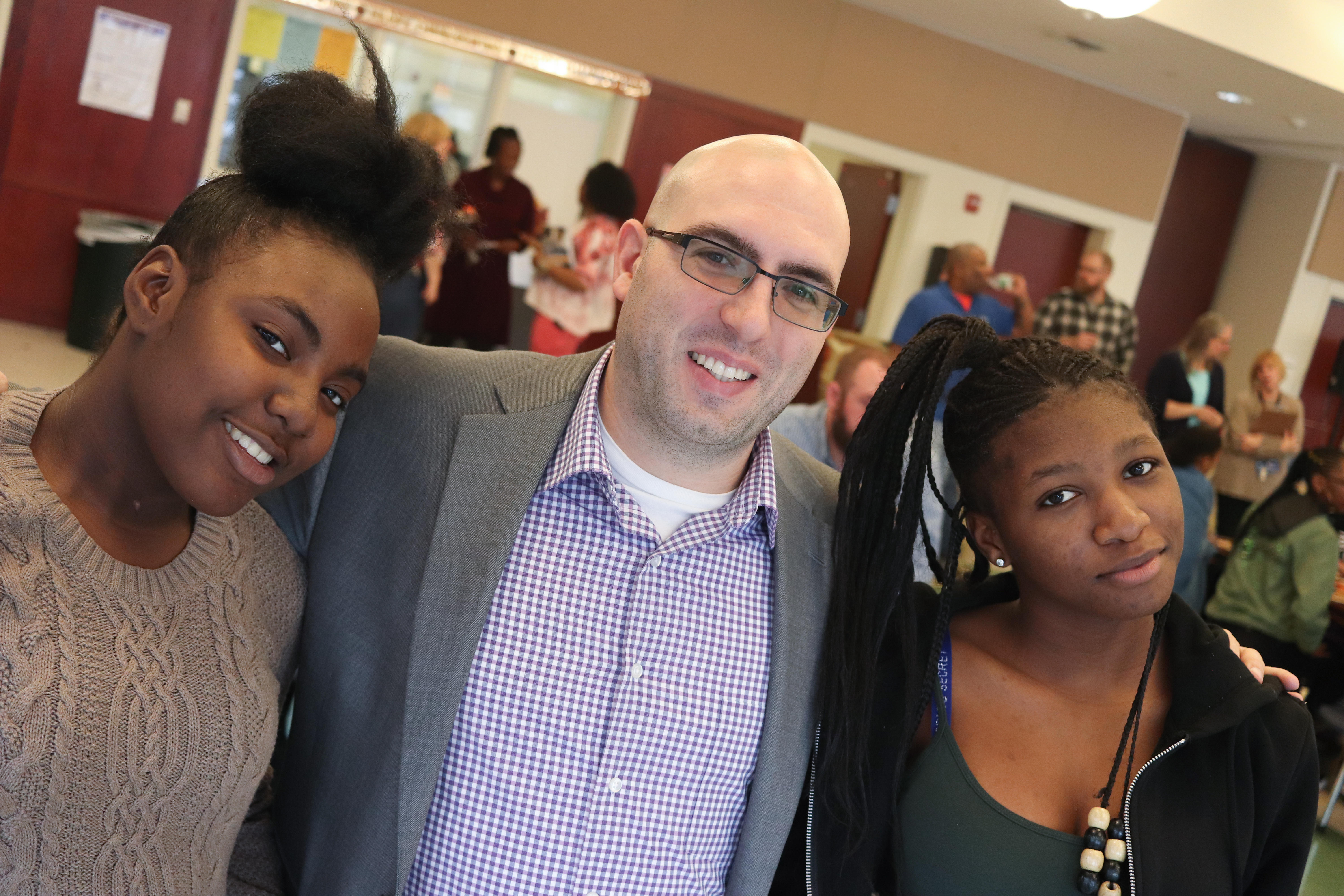 Two female students and Principal William Rivers smiling for a group picture in the cafeteria.