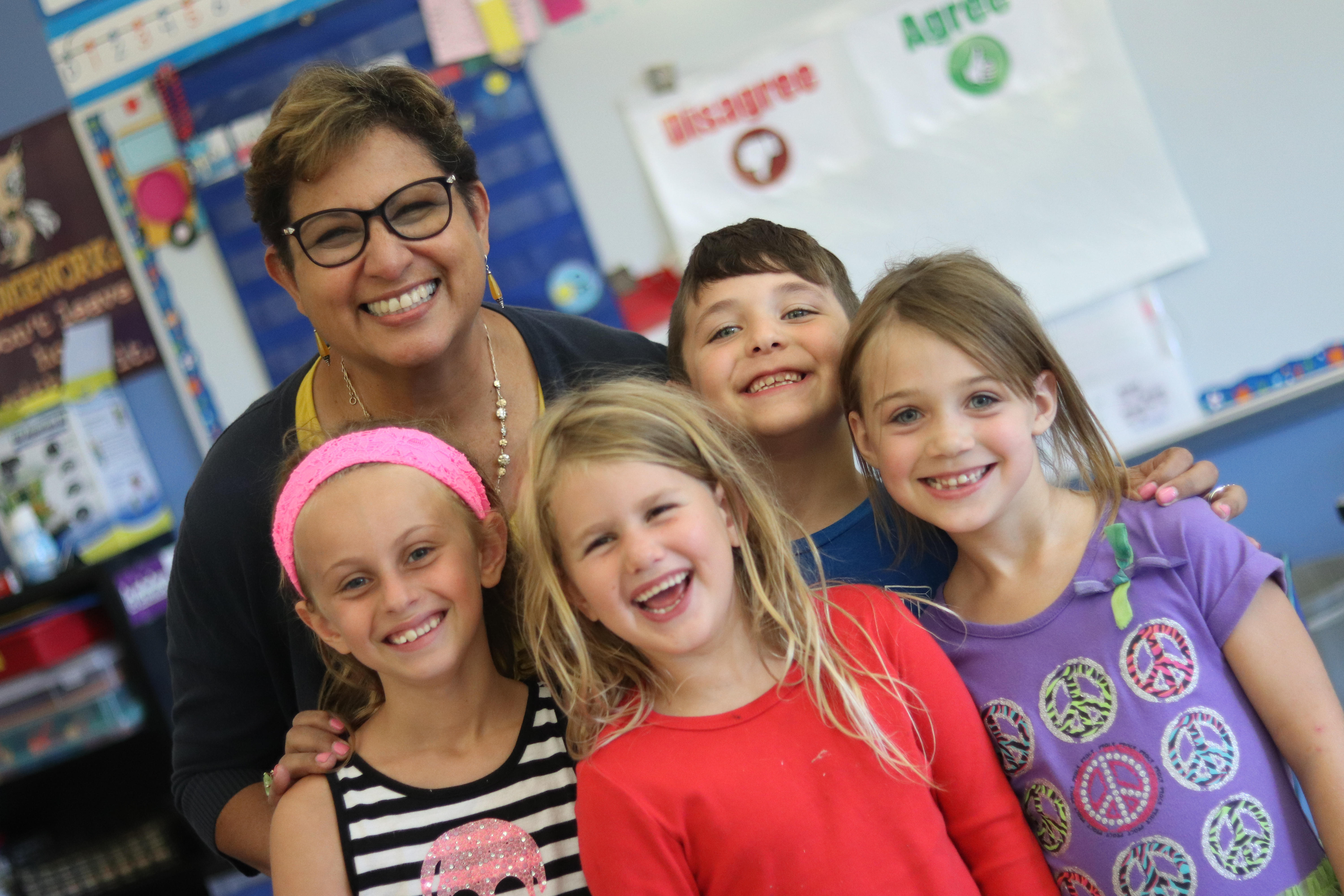 Teacher smiling with a group of students.