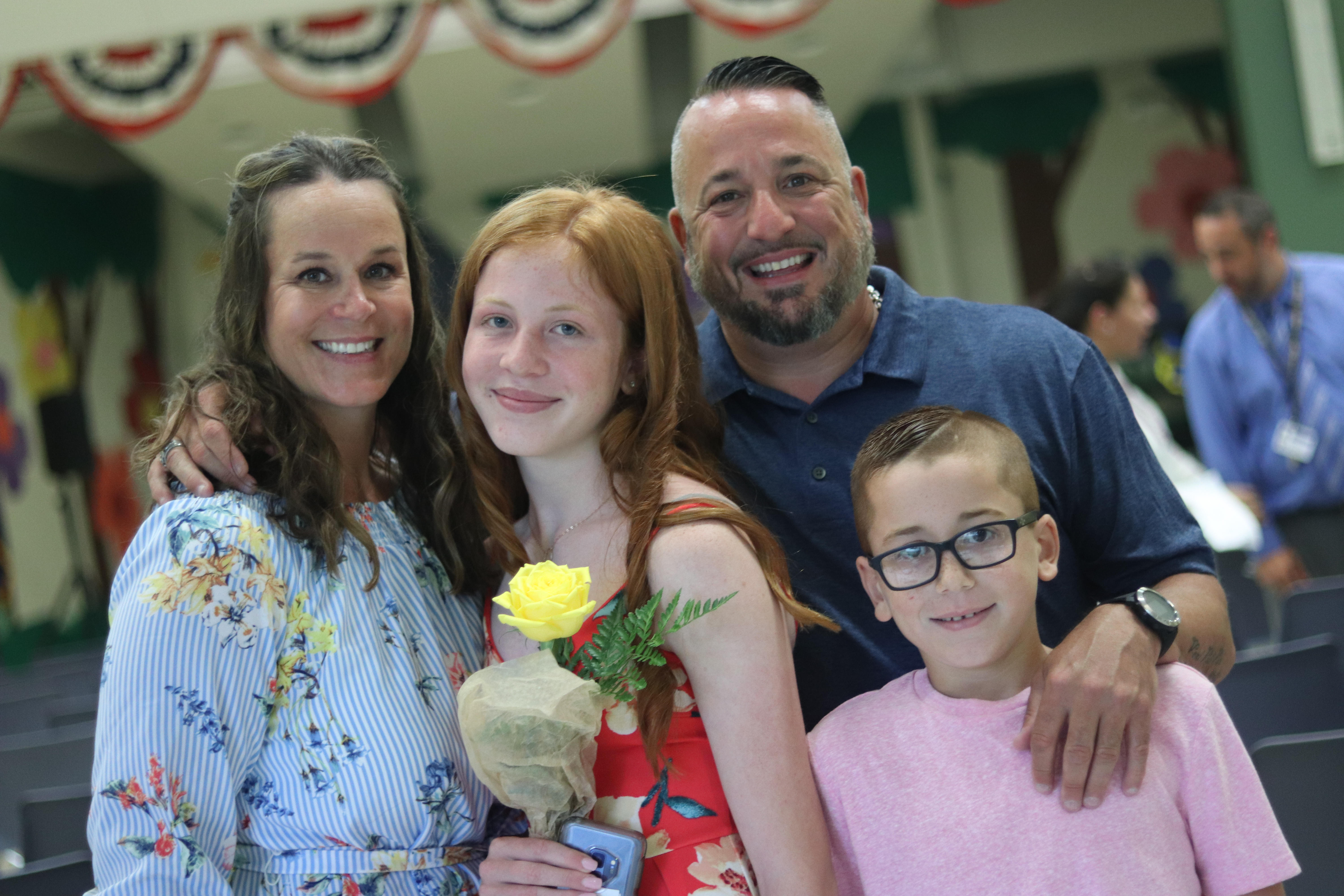 An Eagle Point family smiling for a picture during a sixth-grade promotion ceremony.