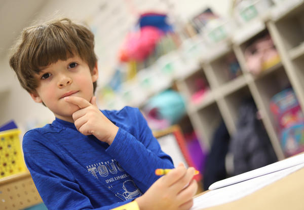 A New Scotland student strikes a pensive pose while working at his desk.