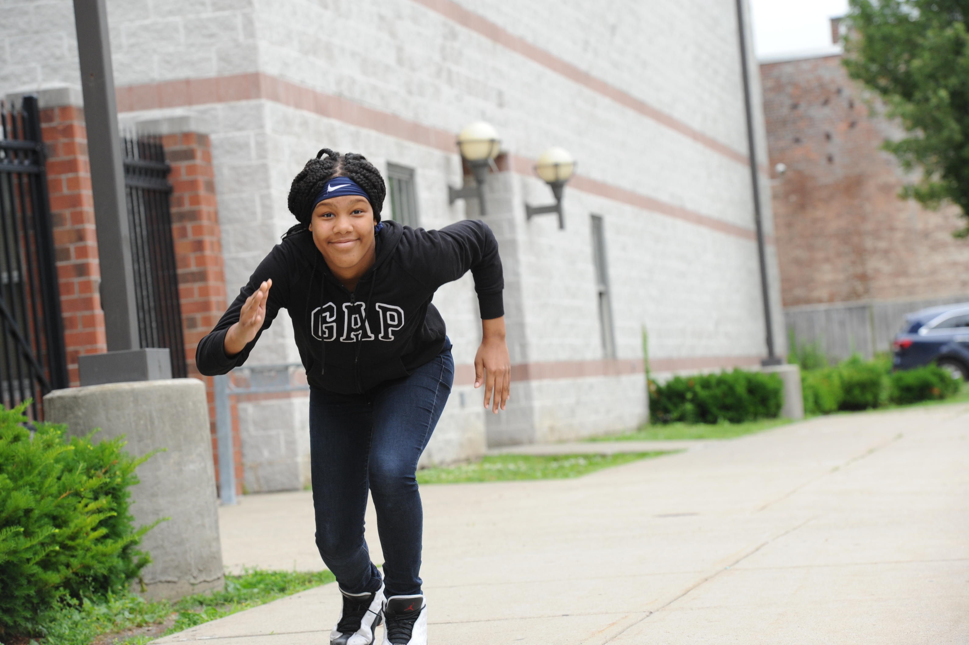 Female student practicing running track outside the school.