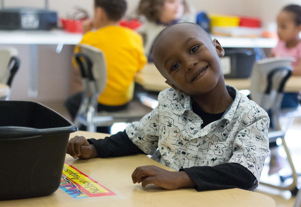 Student smiling in her seat at Pine Hills Elementary School