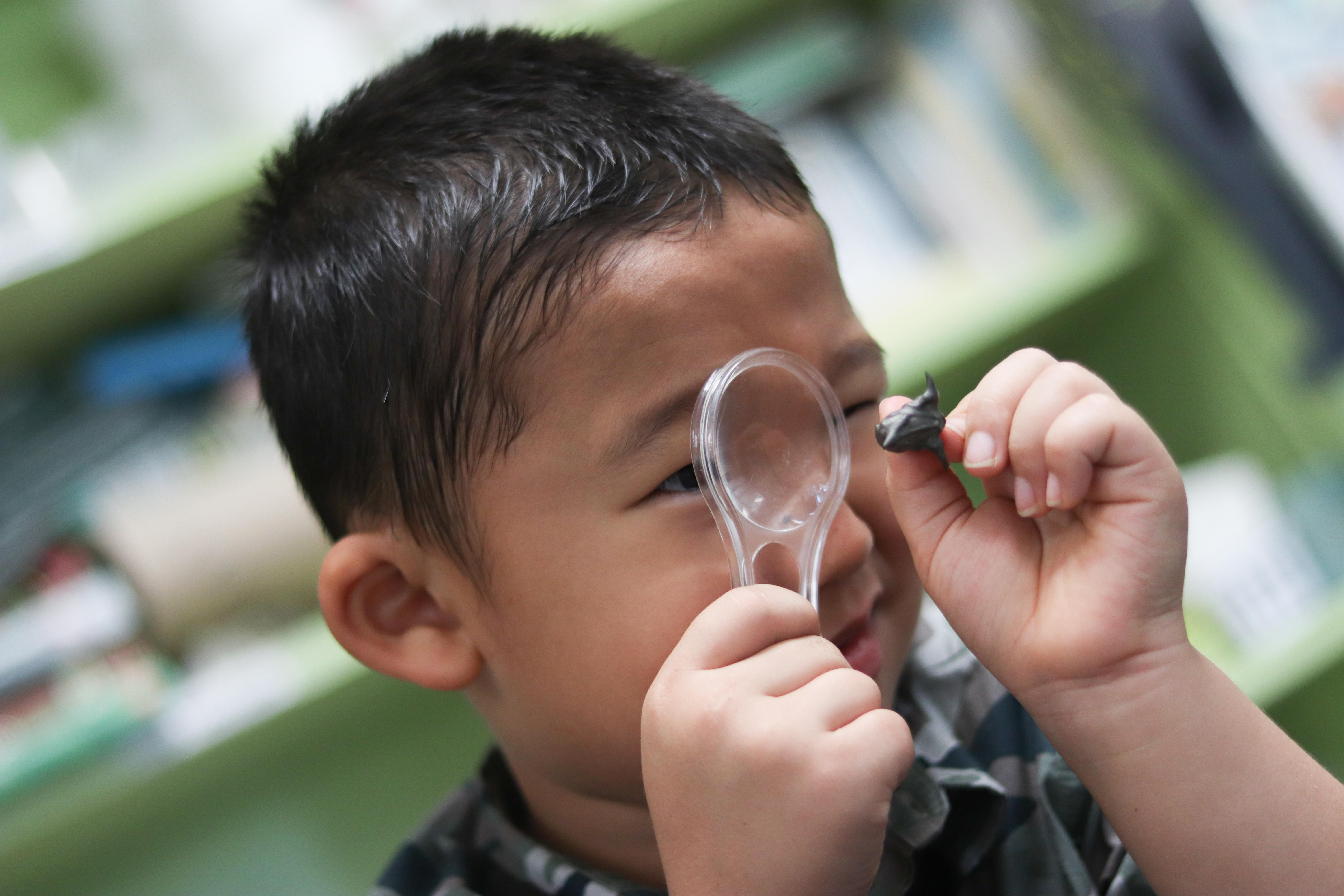 Male student inspecting a seed through a magnifying glass.