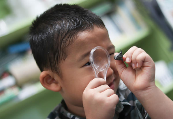 TOAST student using a magnifying glass for an experiment.