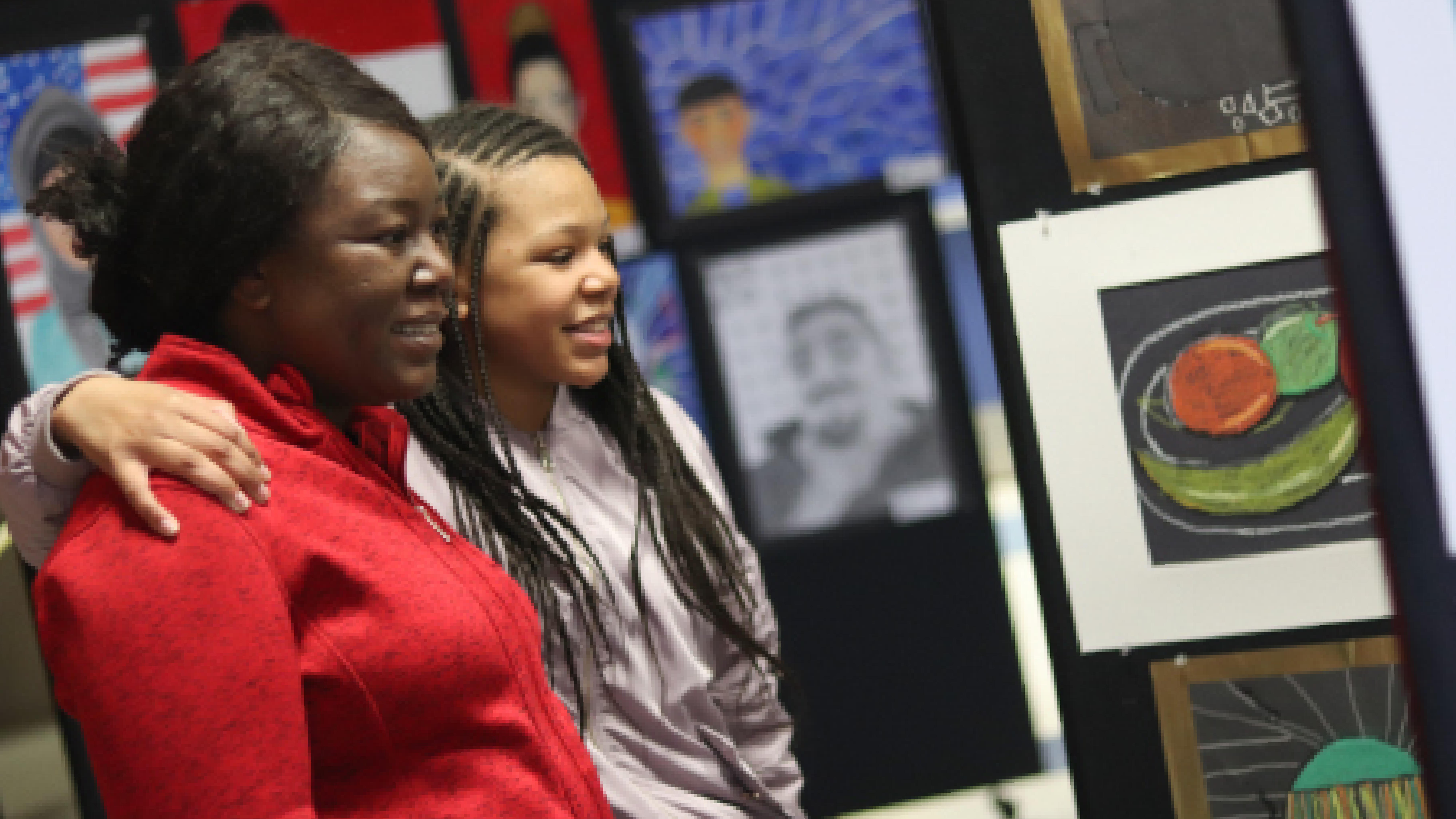 Female student and her mother admiring artwork at an exhibition.