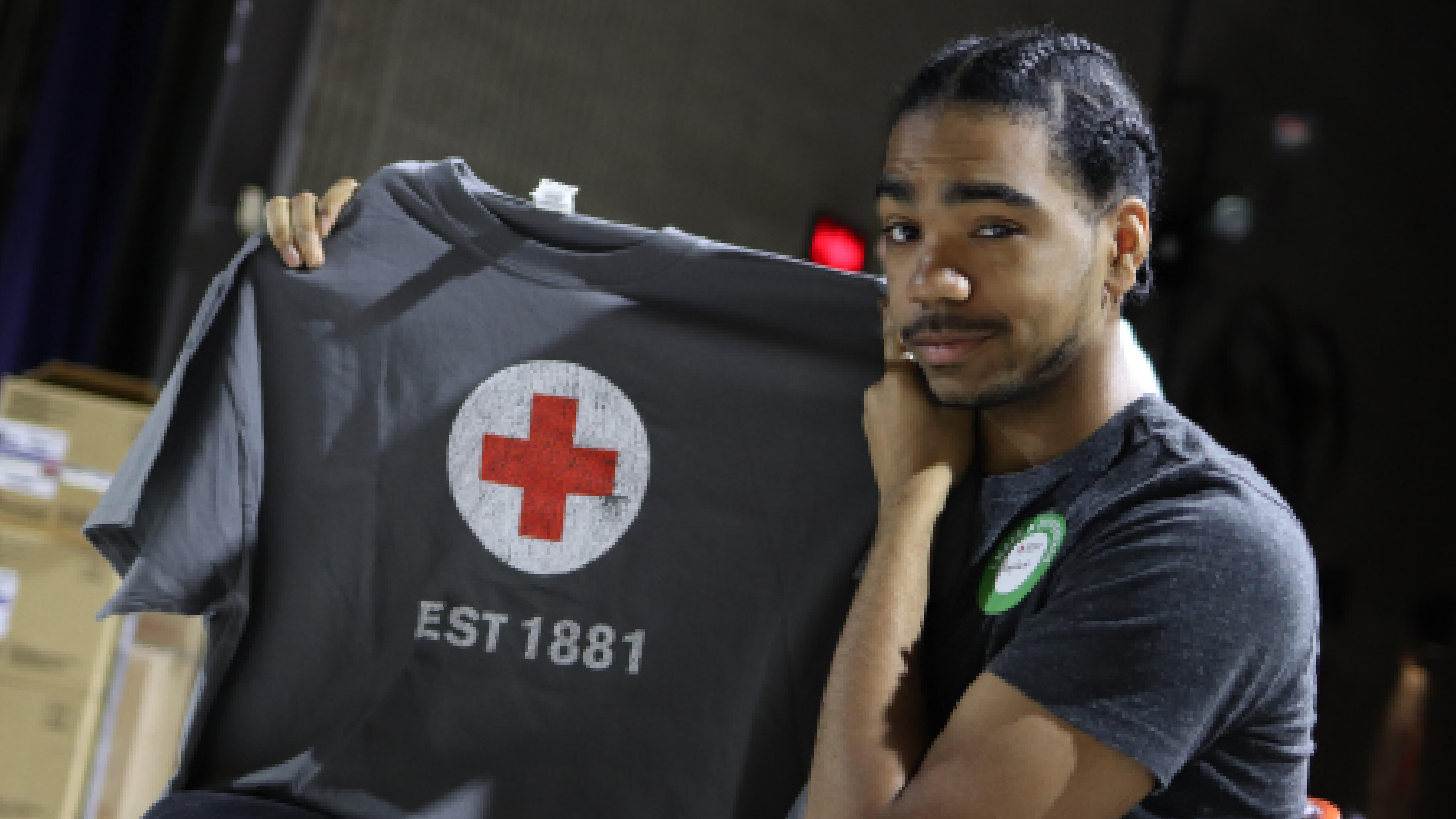 Male student holding up a Red Cross t-shirt after giving blood.