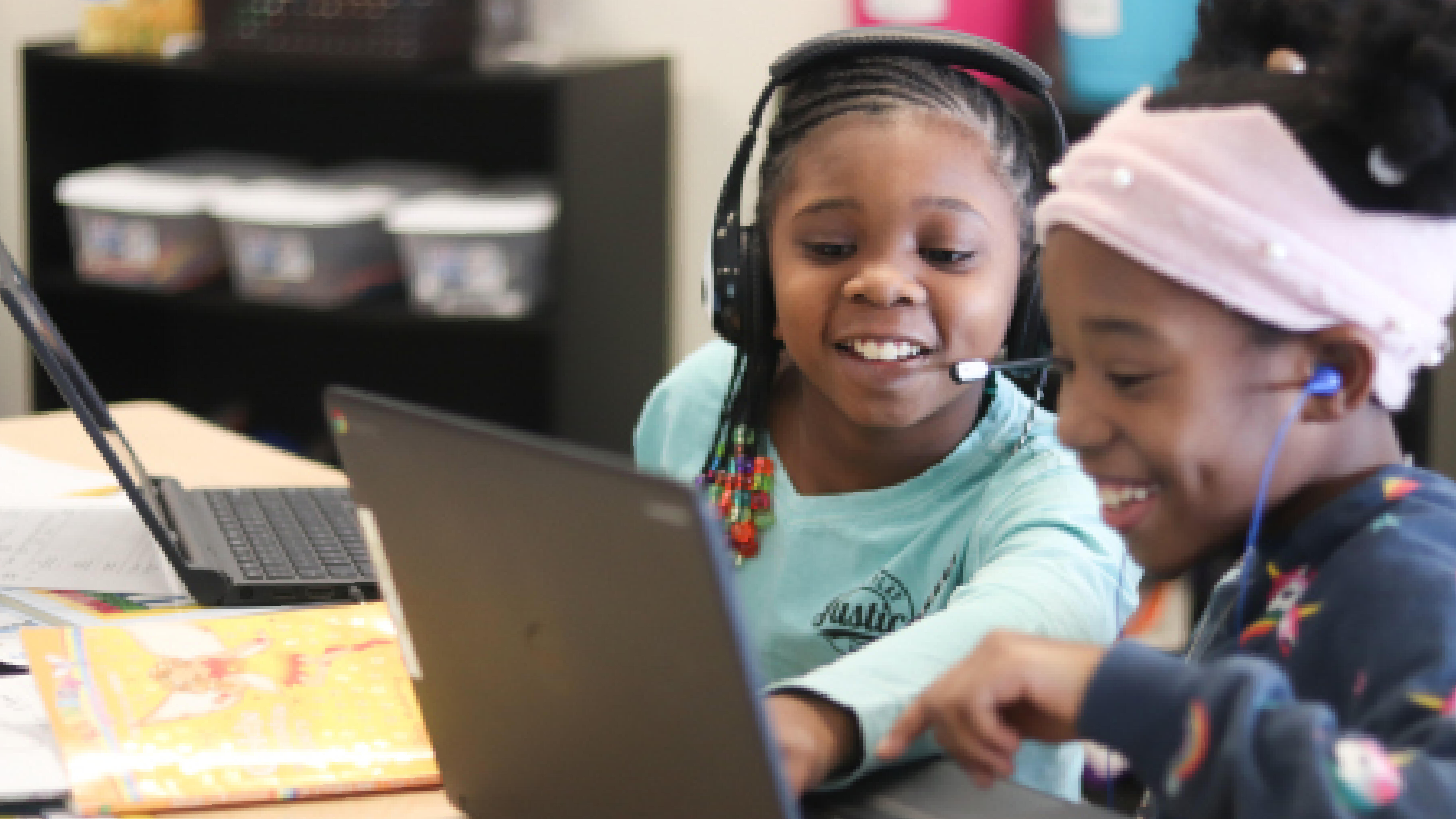 Two female students working collaboratively on a laptop.