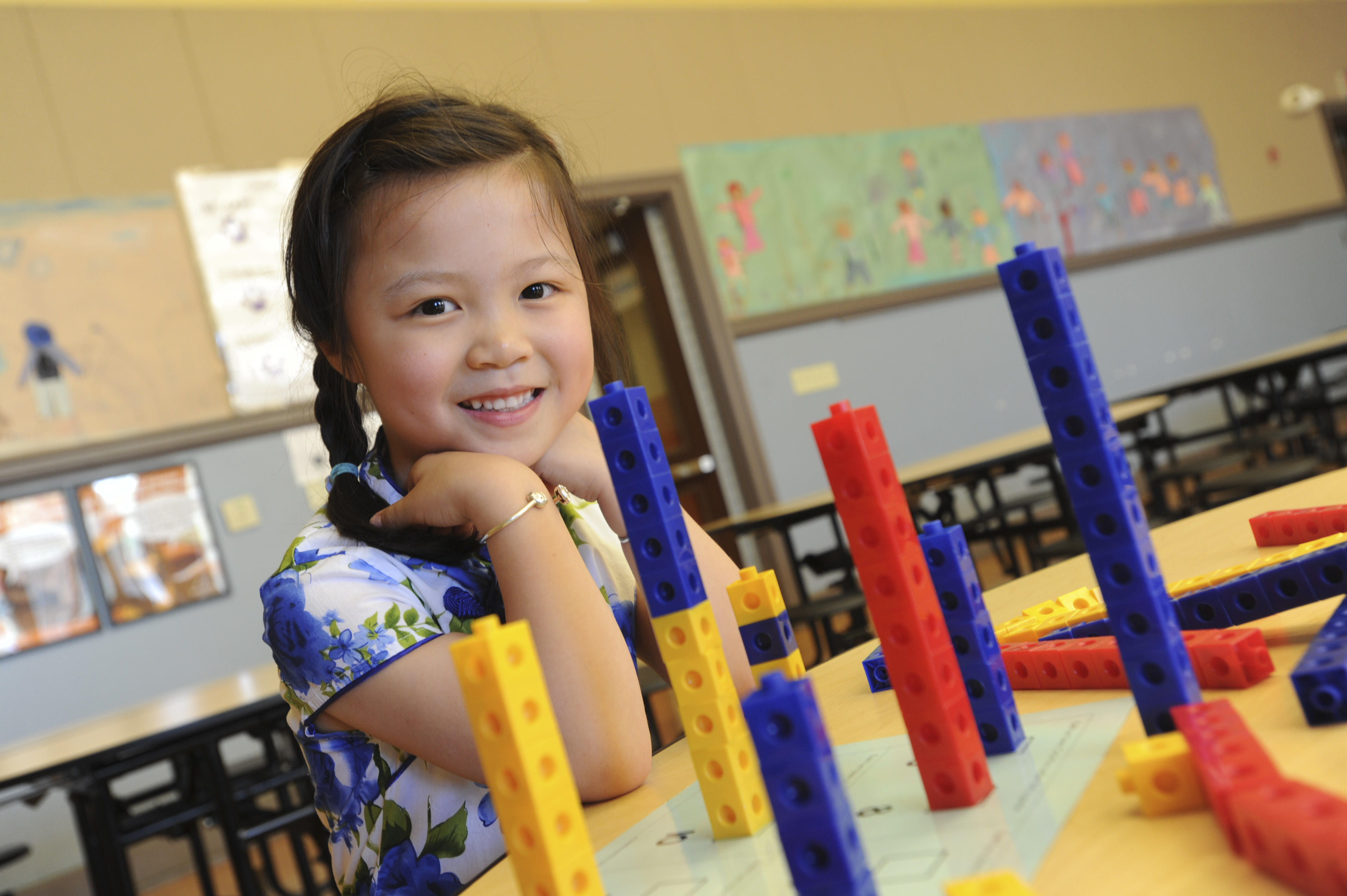 Female student smiling while building with manipulative blocks.