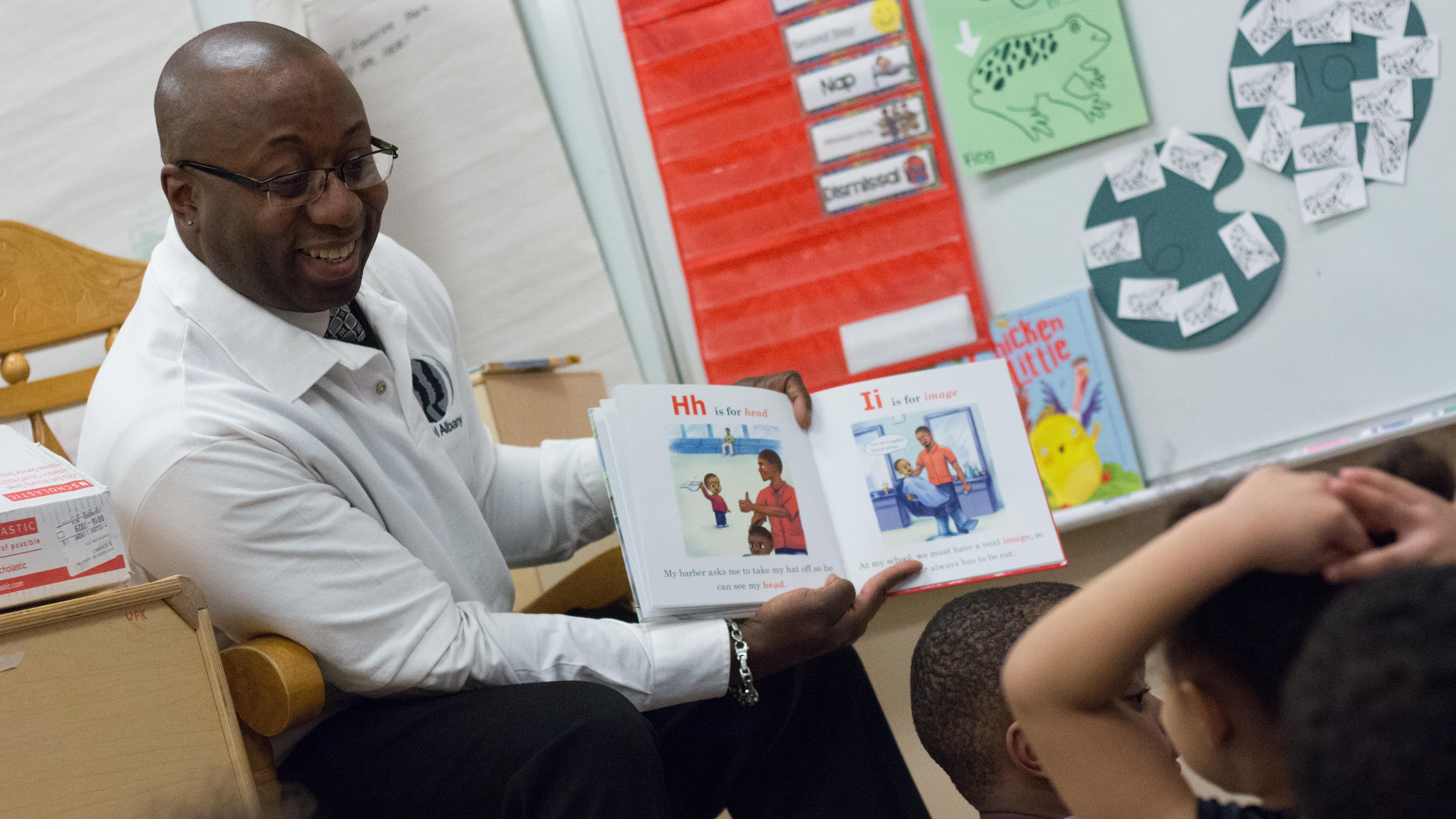 Volunteer reading a book to elementary children.