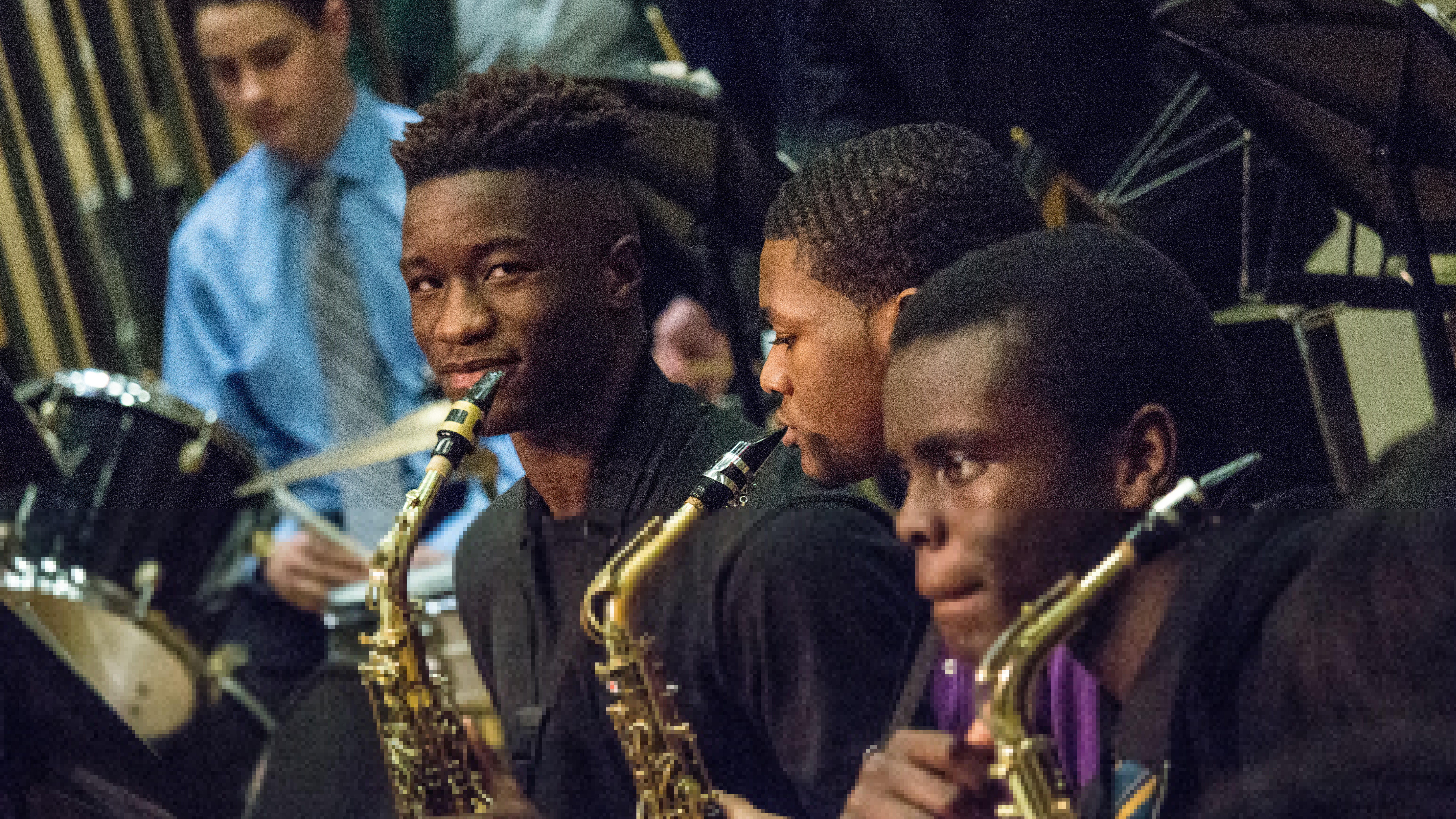 Students playing saxophone during a concert.