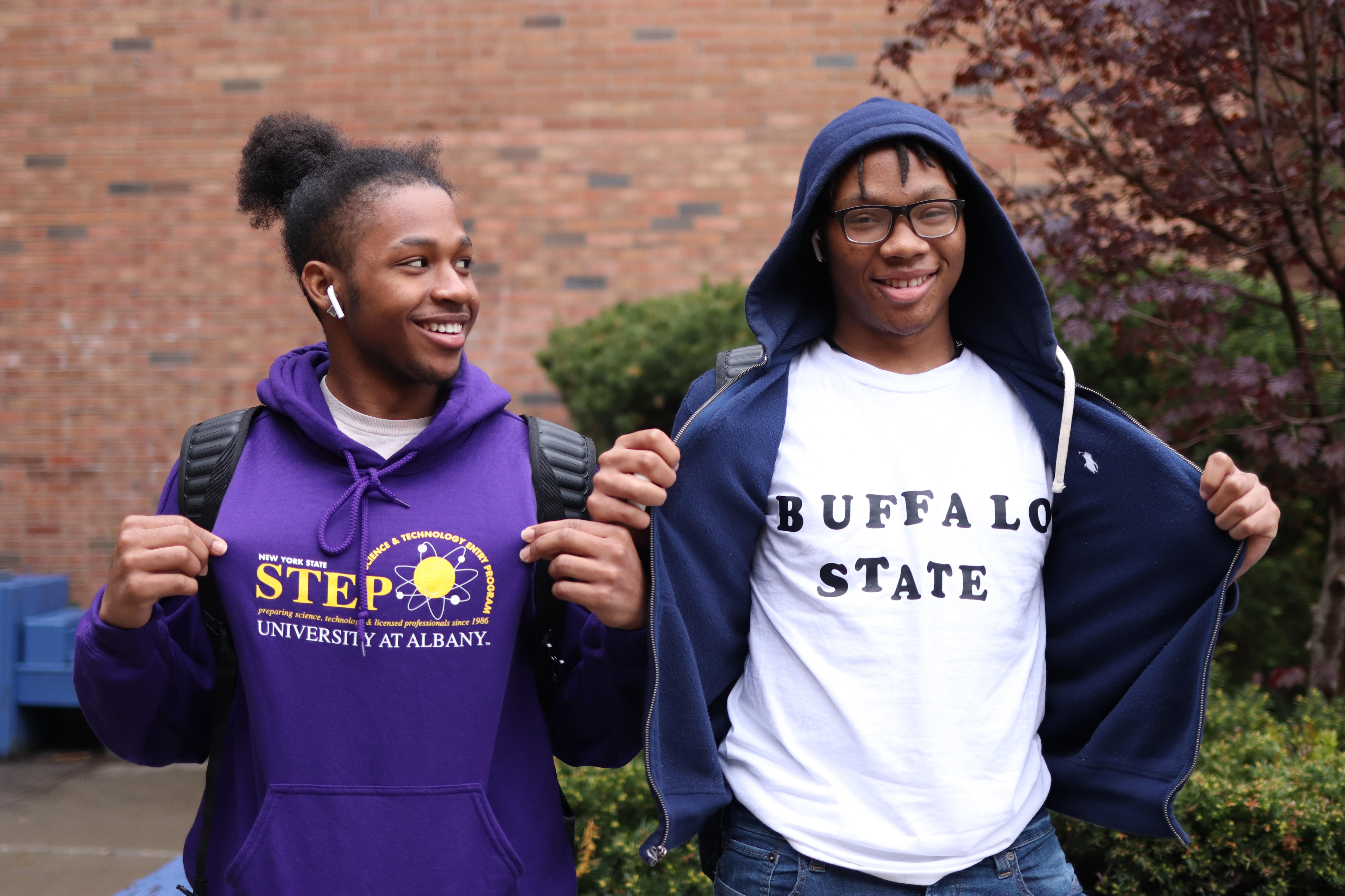 Two students showing off their college t-shirts.