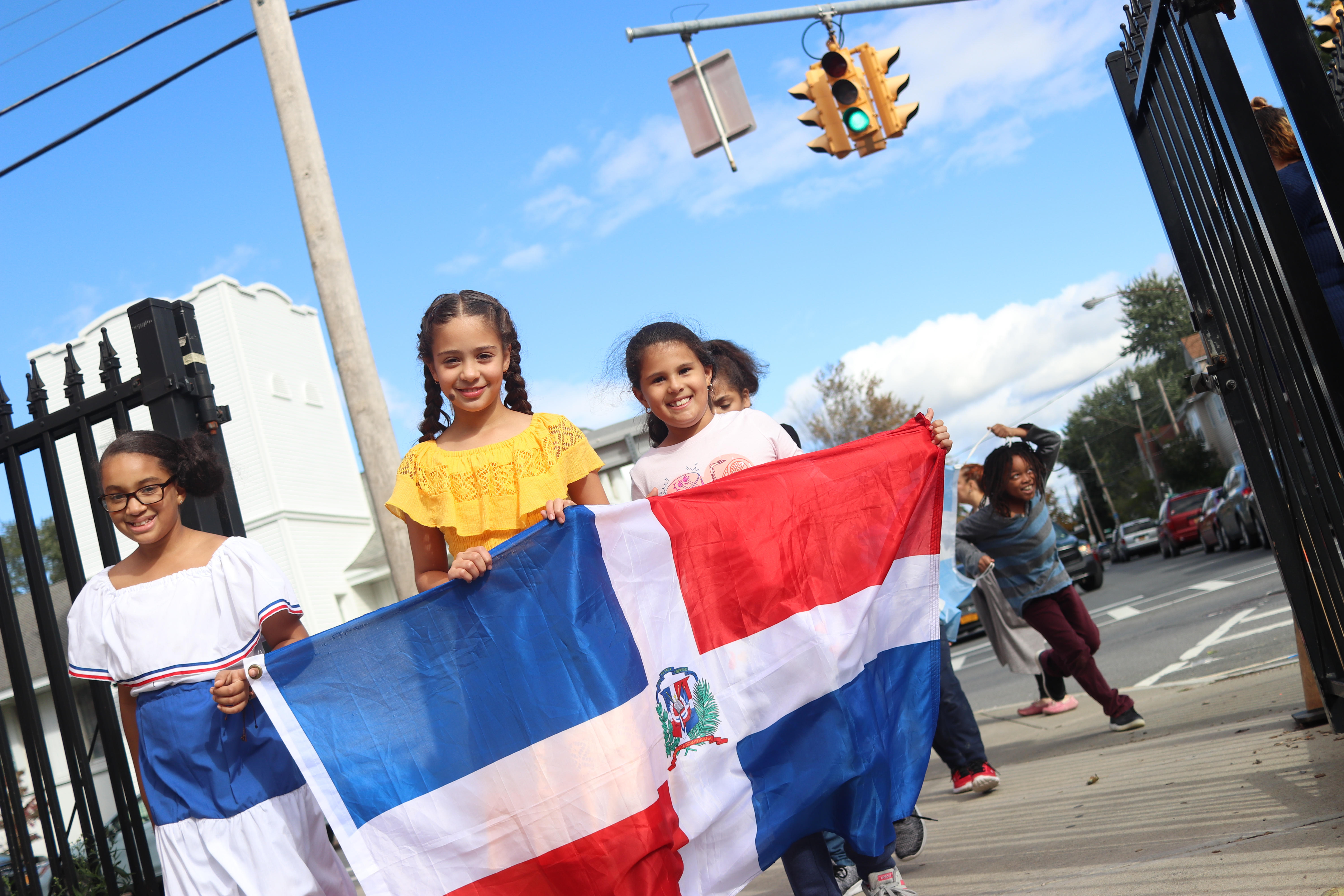 Three students walking with a flag during a Hispanic Heritage parade.