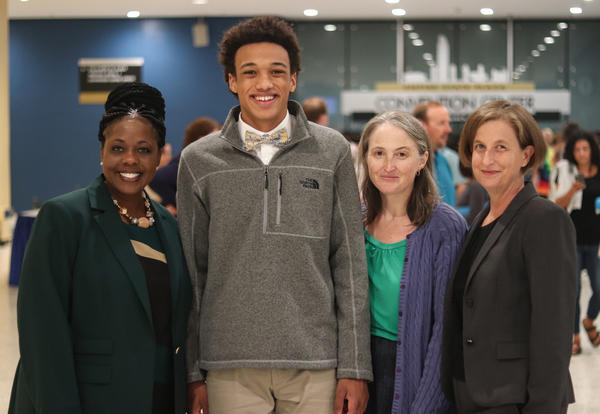Student presenter smiling for a picture with the superintendent and board president.