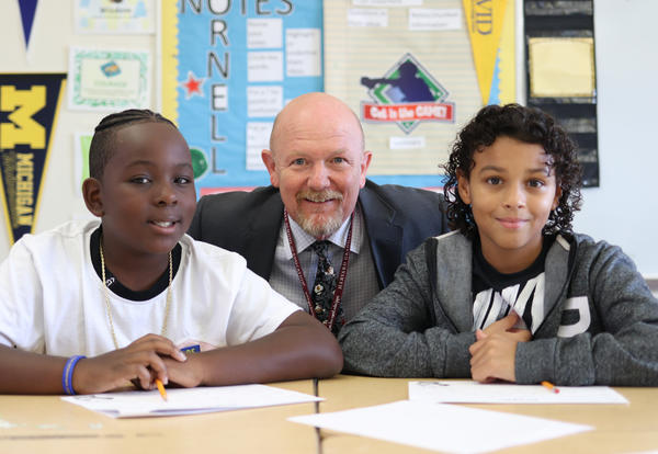 Principal Kenneth Lein posing for a photo with two students at their desks.