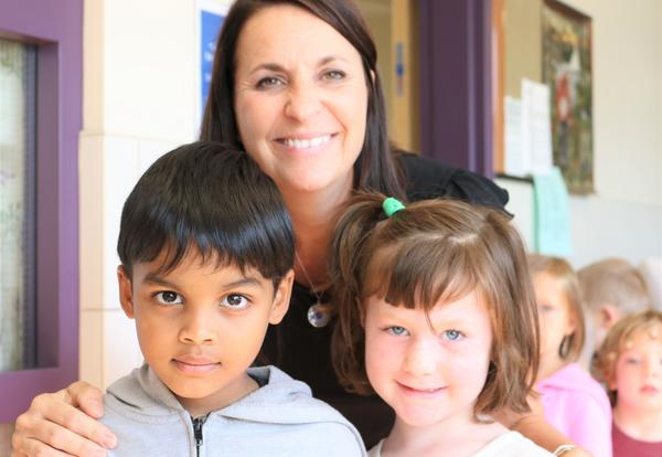 PK/K teacher Carole Battistello poses with students on the first day of school