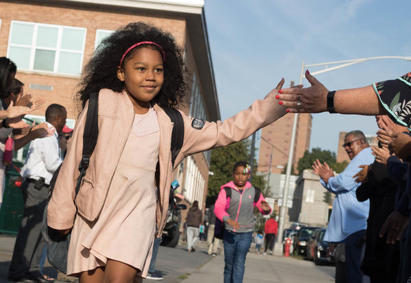 Smiling girl getting welcomed as she enters school