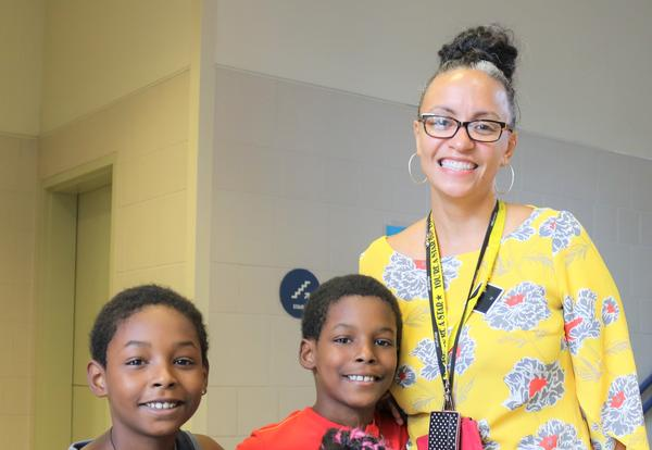 Principal Gayle poses with three students on the first day of school.